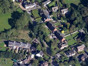 An aerial view of our village showing the large number of trees in our rear garden and the hedges surrounding our land