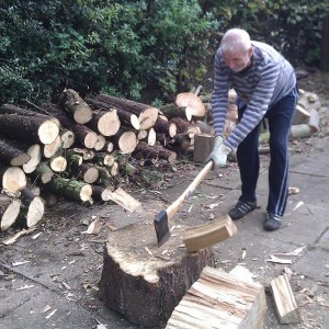 My father enjoying himself with a large axe making firewood for our log burner