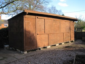 The completed shed with a door at each end and shutters covering an window opening